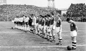 24 May 1964; Republic of Ireland players, from right to left, Joe Haverty, Millwall, Paddy Ambrose, Shamrock Rovers, Willie Browne, Bohemians, Eddie Bailham, Shamrock Rovers, Tony Dunne, Manchester United, Johnny Giles, Leeds United, Andy McEvoy, Blackburn Rovers, Mick McGrath, Blackbrun Rovers, Fred Strahan, Shelbourne, Noel Dwyer, Swansea Town, and Noel Cantwell, Manchester United, captain, stand for the National Anthem before the game. International Friendly, Republic of Ireland v England, Dalymount Park, Dublin. Picture credit; Connolly Collection / SPORTSFILE